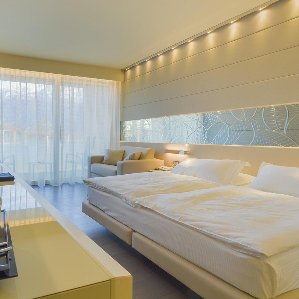 Camere e suites: JUNIOR suite: Moderne e luminose, sui toni chiari, accolgono l'ospite con grandi vetrate vista lago o vista giardino e sulle montagne che circondano il lago. Park Hotel Imperial